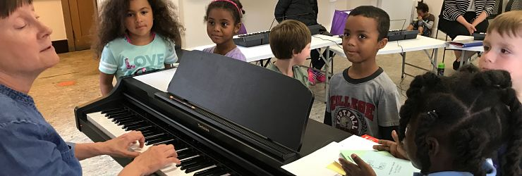 Children in beginning keyboard class learn a new song